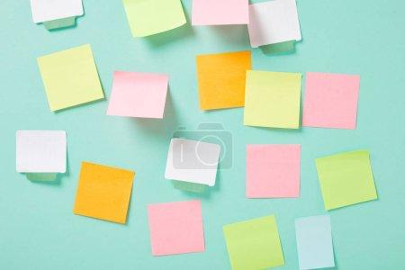 Photo pour Notes collantes vides multicolores avec espace de copie sur mur turquoise - image libre de droit
