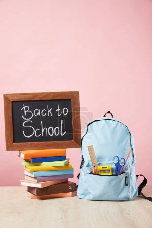 Photo for Blue backpack with supplies in pocket near chalkboard with back to school lettering on books isolated on pink - Royalty Free Image
