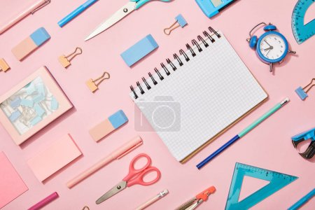 flat lay with blue and pink school supplies and blank notebook isolated on pink