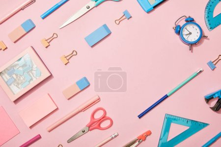 flat lay with blue school supplies and copy space isolated on pink
