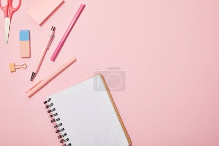 Photo for Top view of scattered school supplies near blank notebook isolated on pink - Royalty Free Image