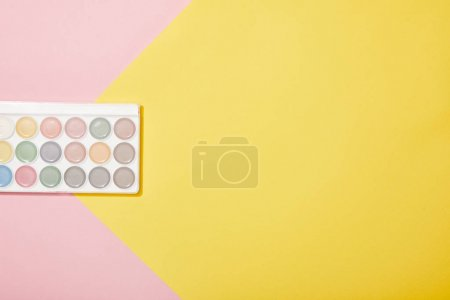 Photo for Top view of watercolor paints on pink and yellow background - Royalty Free Image