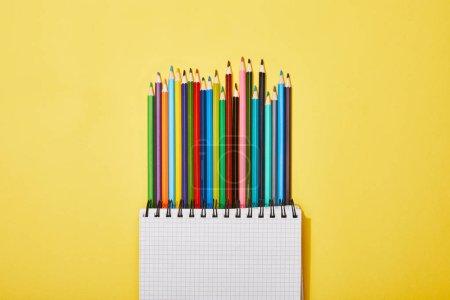 Photo pour Vue supérieure des crayons colorés près du cahier blanc sur le jaune - image libre de droit
