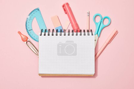 Photo for Top view of blank notebook among school supplies on pink background - Royalty Free Image