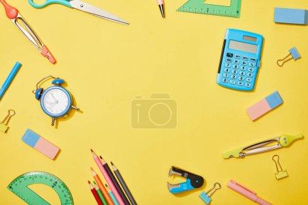 Foto de Vista superior de los útiles escolares dispersos en el fondo amarillo con espacio de copia - Imagen libre de derechos