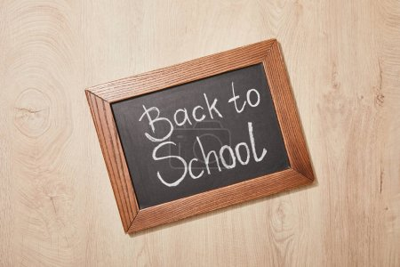 Photo for Top view of chalkboard with back to school lettering on wooden desk - Royalty Free Image