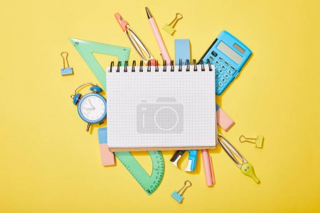 Photo for Top view of school supplies scattered on yellow background with empty notebook - Royalty Free Image