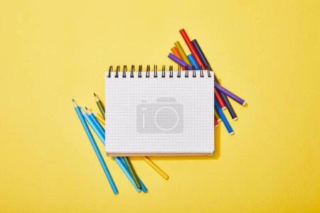 Photo pour Vue du haut des crayons de couleur et des stylos en feutre dispersés près du cahier blanc sur le jaune - image libre de droit