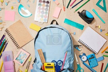Foto de Vista superior de varios útiles escolares con mochila azul en el escritorio de madera - Imagen libre de derechos