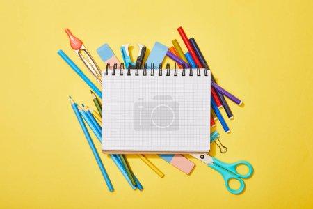 Photo pour Vue du haut des crayons de couleur, ciseaux, caoutchoucs et feutres éparpillés près du bloc-notes vierge sur jaune - image libre de droit