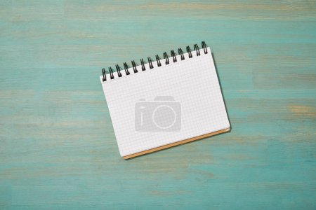 Photo for Top view of empty blank notebook on wooden turquoise desk - Royalty Free Image