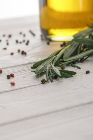 Photo for Rosemary bundle near bottle with oil and scattered red and black peppercorns on white wooden surface - Royalty Free Image