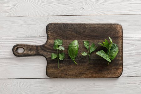 Photo for Top view of brown wooden cutting board with parsley, basil, cilantro and peppermint leaves on white surface - Royalty Free Image