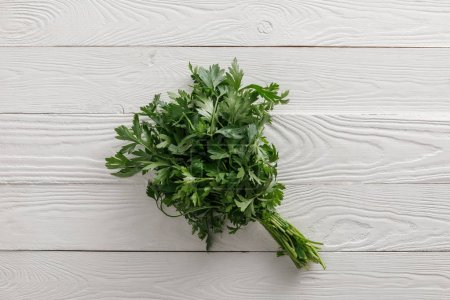 Photo for Top view of fresh green parsley bundle on white wooden surface - Royalty Free Image