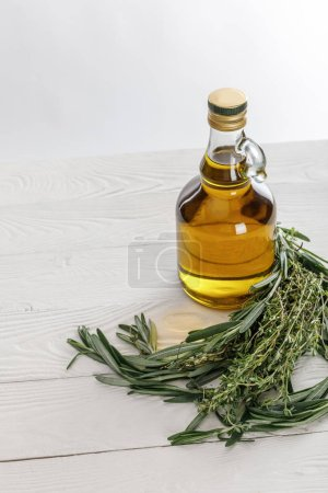 Photo for Bottle of oil near rosemary and thyme bungs on white wooden table isolated on grey - Royalty Free Image