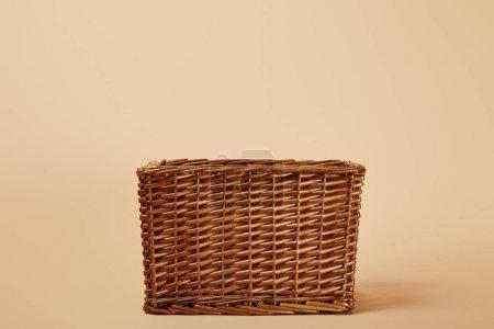 Photo pour Panier en osier brun naturel sur fond beige - image libre de droit
