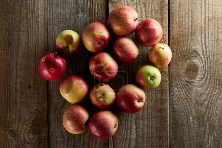 Photo for Top view of ripe juicy apples on brown wooden surface - Royalty Free Image