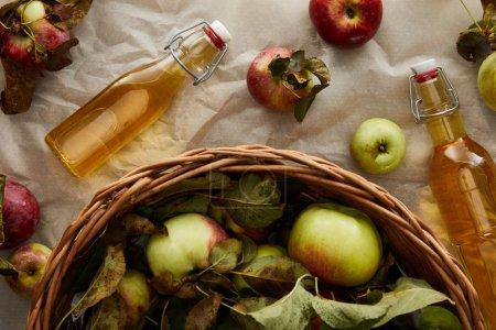 Photo pour Vue supérieure du panier avec des pommes près des bouteilles en verre avec le cidre - image libre de droit