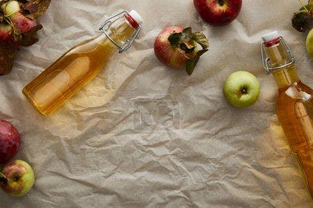 Photo pour Vue du dessus des bouteilles de cidre près des pommes éparpillées avec espace de copie - image libre de droit