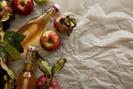 Photo pour Vue du dessus des bouteilles de cidre près des pommes avec espace de copie - image libre de droit
