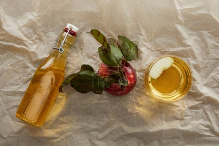 Photo for Top view of apple, bottle and glass of fresh cider on parchment paper with copy space - Royalty Free Image