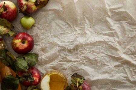 Photo for Top view of apples with leaves and glass of cider on parchment paper with copy space - Royalty Free Image