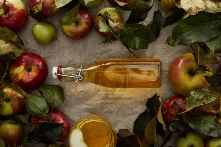 Photo for Top view of bottle with cider between apples and glass with drink on parchment paper with copy space - Royalty Free Image