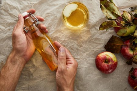 Photo for Cropped image of man holding bottle of apple cider under parchment paper with apple and glass - Royalty Free Image