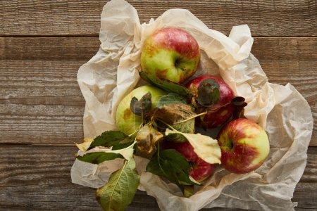 Photo pour Vue supérieure des pommes mûres avec des feuilles sur le papier parchemin froissé sur la surface en bois - image libre de droit