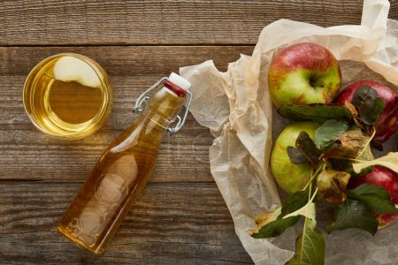 Photo for Top view of creased parchment paper with apples near bottle and glass of cider on wooden surface - Royalty Free Image