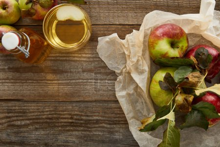 Photo for Top view of parchment paper with apples near bottle and glass of cider on wooden surface - Royalty Free Image