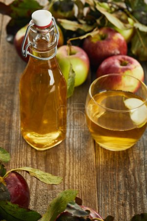 Photo for Bottle of fresh cider near glass and apples on wooden surface - Royalty Free Image