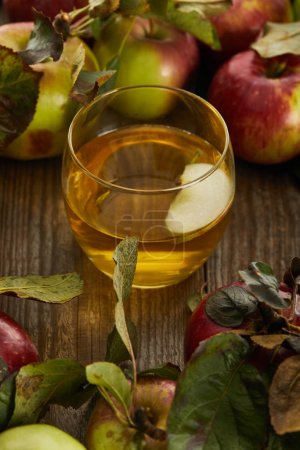 Photo for Glass of fresh cider with slice near apples on wooden surface - Royalty Free Image