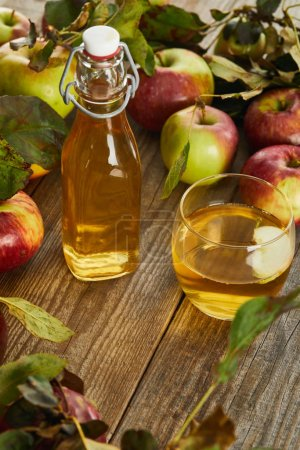 Photo for Bottle and glass of fresh cider on wooden surface with ripe apples - Royalty Free Image
