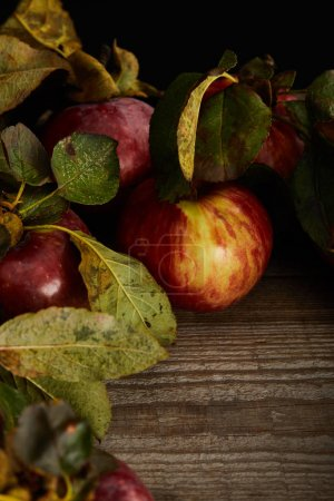 Photo for Fresh ripe red apples with leaves on wooden surface - Royalty Free Image