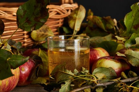 Photo for Glass of cider near wicker basket and apples - Royalty Free Image