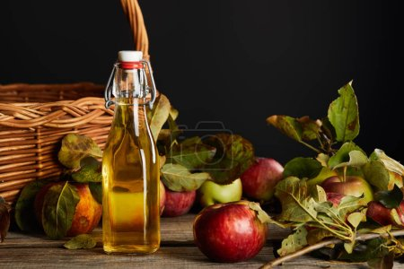 Photo for Bottle of cider near wicker basket and apples on wooden surface isolated on black - Royalty Free Image