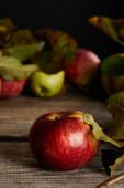 """Постер, картина, фотообои """"красные спелые яблоки с листьями на деревянной поверхности изолированы на черном"""""""