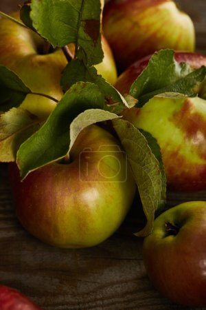 Photo for Close up view of juicy fresh apples with leaves on wooden surface - Royalty Free Image