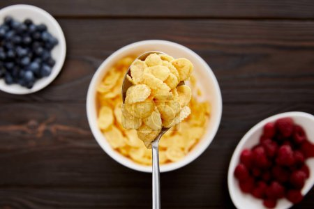 Photo for Top view of spoon with cornflakes above wooden surface with berries - Royalty Free Image
