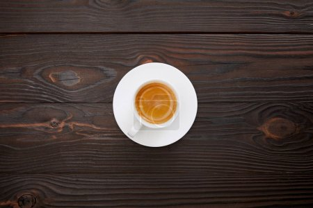 Photo for Top view of cup of coffee with saucer on wooden surface - Royalty Free Image