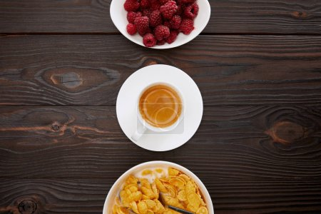 Photo for Top view of bowl with cornflakes and milk near cup of coffee and plate of raspberry on wooden surface - Royalty Free Image