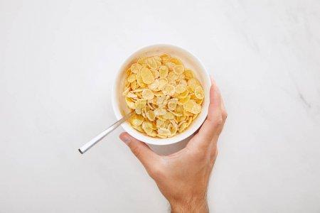 imagen recortada de hombre sosteniendo tazón blanco con copos de maíz sobre fondo de mármol