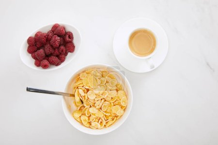 Photo for Top view of bowl of cornflakes with spoon near cup of coffee and plate with raspberry on white marble surface - Royalty Free Image
