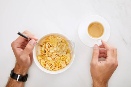 cropped image of man holding cup of coffee and spoon in bowl with cornflakes on white marble background