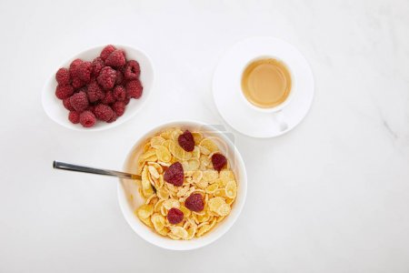 Photo for Top view of bowl of cornflakes with raspberry near cup of coffee and plate with fresh berries on white marble surface - Royalty Free Image