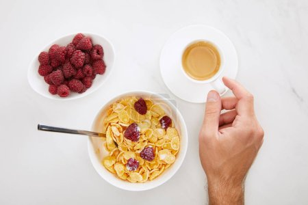 Photo for Cropped image of man holding cup of coffee near bowl with cornflakes and plate with fresh raspberry on white marble background - Royalty Free Image