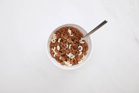 Photo for Top view of bowl with chocolate and white cereal and spoon on marble surface - Royalty Free Image