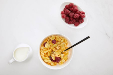 Photo for Top view of cornflakes bowl near fresh raspberry and milk jug on white marble surface - Royalty Free Image