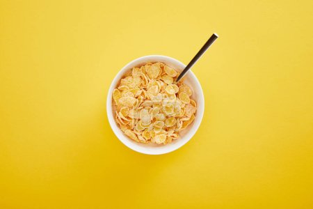 Photo for Top view of bowl with cornflakes isolated on yellow - Royalty Free Image